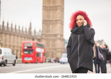 Beautiful redhair woman talking on mobile in London with Big Ben and Westminster palace on background and traffic passing behind her.