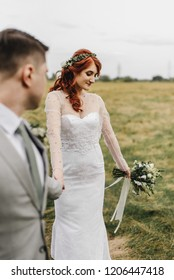Beautiful red-haired bride and groom hold hands in a field landscape