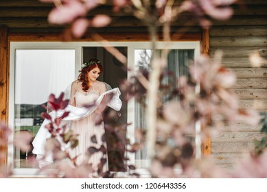 Beautiful red-haired bride holding a wedding dress