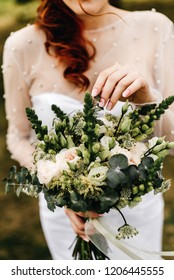 Beautiful red-haired bride holding a wedding bouquet