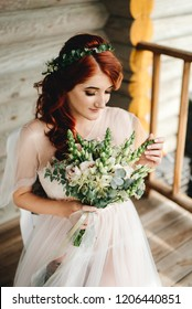 Beautiful red-haired bride sits with a wedding bouquet
