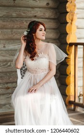 Beautiful red-haired bride touches herself by the hair