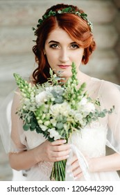 Beautiful red-haired bride with a wedding bouquet looks into the camera