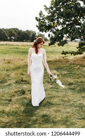 Beautiful red-haired bride with a wedding bouquet stands on a beautiful landscape field