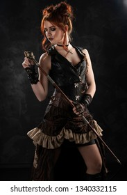A beautiful red-haired cosplayer girl wearing a Victorian-style steampunk costume with a big breast in a deep neckline thoughtfully holds a cane in her hands on a dark background. Copy space.