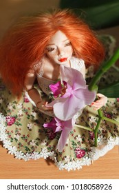 Beautiful red-haired doll and orchid flower close-up