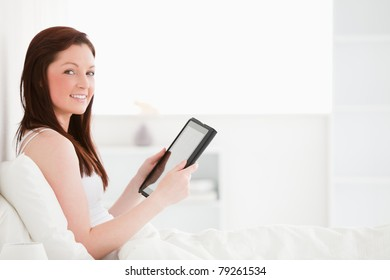 Beautiful red-haired female reading a book while sitting on her bed