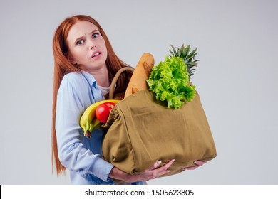 beautiful redhaired ginger woman holding eco cotton bag full of products: banana, pineapple,vegetables.