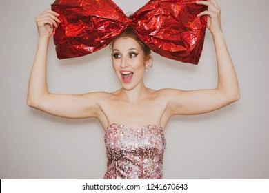 beautiful red-haired girl with a big red bow of wrapping paper on her head and tongue hanging out looking at the camera on a light background