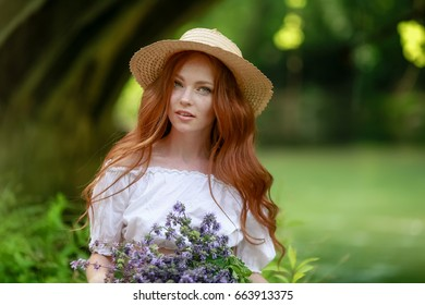 Beautiful red-haired girl with freckles in a hat with field flowers on the nature by the river