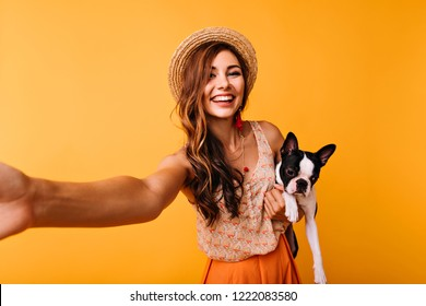 Beautiful red-haired girl with french bulldog making selfie. Inspired female model posing on orange background with black puppy.