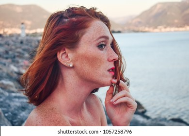 Beautiful red-haired girl on the sea.