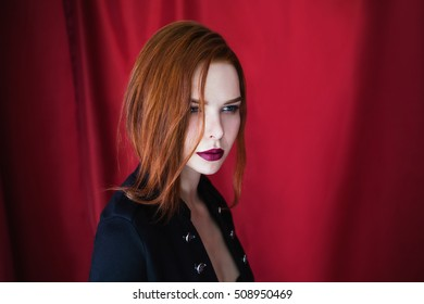 Beautiful red-haired girl with parted lips in black lingerie on red background looking away. Fashion photography. Bright appearance. Red hair. Portrait in profile
