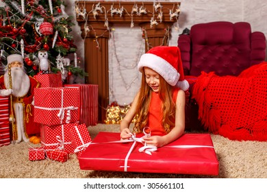 Beautiful red-haired girl in santa hat opening gift near Christmas tree