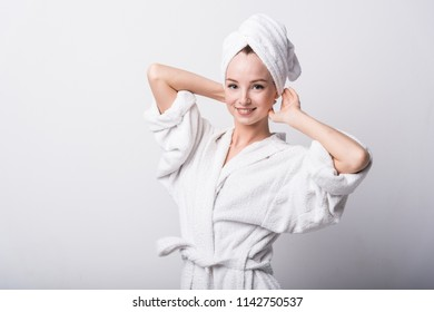 Beautiful red-haired girl in a white bathrobe with a towel on her head on a light background