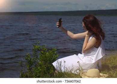 beautiful red-haired girl in a white summer dress uses a cell phone sitting on the shore and rivers, sunlight