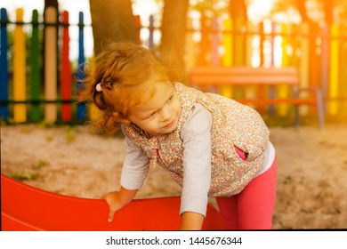 A beautiful red-haired little girl plays in a childrens park on the cand  camera lens catches  picks up the orange sunset lights from the sun.