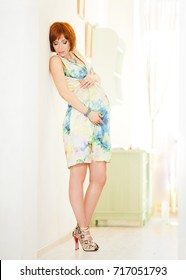 beautiful red-haired pregnant woman in a dress standing in a bright room and touching the tummy
