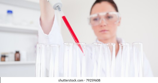 Beautiful red-haired scientist filling up a test tube in a lab