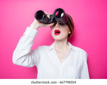 Beautiful red-haired surprised businesswoman with binoculars on pink background