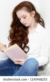 Beautiful red-haired teen girl wearing in jeans and blouse reading a book. Beauty, fashion.