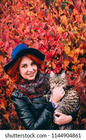 Beautiful red-haired woman in blue hat and leather jacket walking with cat in autumn red park. Female stands against a background of brightly red leaves with a furry kitty and smiles. Portrait view