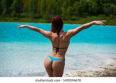 A beautiful red-haired woman in a blue seductive bikini stands with her back against an unusual turquoise lake. A miracle of nature, bright blue clear water. Maldives. Ash dump, poisoned water.