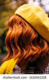 A beautiful red-haired woman with a curly hairstyle walking in the park. Fashionable autumn clothes in orange mustard tones. Close-up portrait. Incognito, no face faceless