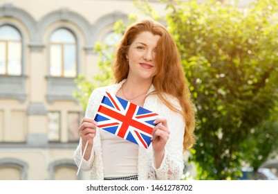 Beautiful red-haired woman with a flag of Great Britain. Travel and learn English.