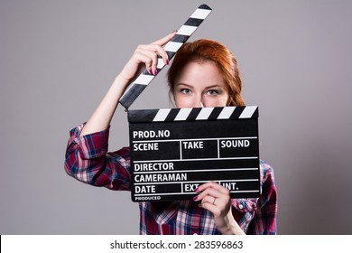 Beautiful red-haired woman holding a movie clapper, isolated over gray background. Girl in plaid shirt helps in shooting a movie