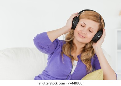 Beautiful red-haired woman listening to music and enjoying the moment while sitting on a sofa in the living room