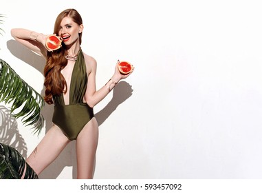 beautiful red-haired woman standing on a white background with a palm tree in a swimsuit bikini and holding a grapefruit cute smile snow-white smile perfect photos for advertisement diets and banner