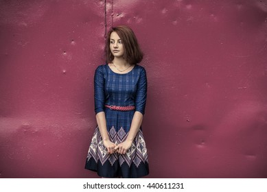 Beautiful red-haired young girl in a blue dress on a background of a metal wall