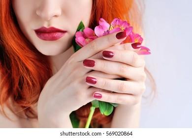 Schöne junge Rothaarige mit Blumen Alstroemeria. Handfokus