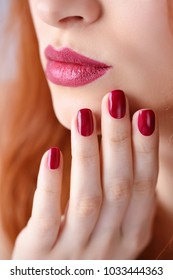 Beautiful red-haired young woman with red manicure, lipstick same color. Close up Portrait.