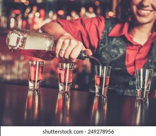 Beautiful redhead barmaid making shots