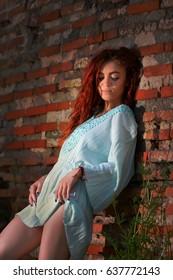 Beautiful redhead with blue eyes posing outdoor near a brick wall