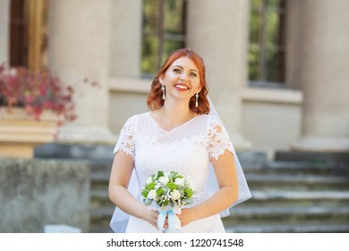 Beautiful redhead bride with bouquet outdoor. Happy bride outdoors. Beautiful bride posing in her wedding day