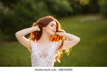 Beautiful redhead Bride playing with her hair. Portrait outdoor in sunset light. Pretty young caucasian redhead girl