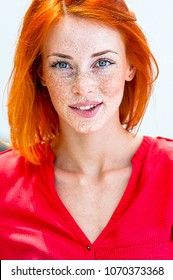Beautiful redhead freckled woman smiling seductive, biting lips