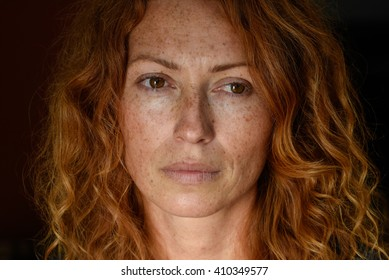 beautiful redhead freckled young woman with glance in eyes without make up black background close up