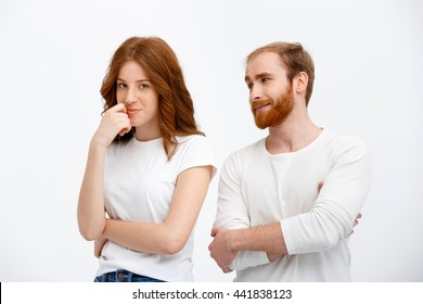 Beautiful redhead girl and boy standing over white background smiling