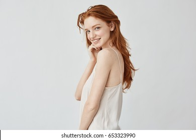 Beautiful redhead girl with freckles smiling looking at camera.