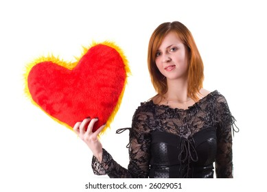 beautiful redhead girl holding a heart pillow on white