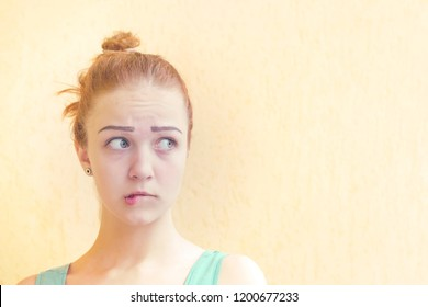 Beautiful redhead girl looking away. Woman having doubtful and indecisive face expression. Nonverbal behavior, body language. Confused young female posing isolated on yellow background with copy space