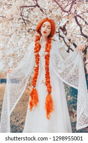 Beautiful redhead girl with plait on spring floral background. Woman in white dress in garden on sakura background. Blooming spring tree in park. Japan girl. Blossom sakura in park. Braided hair.