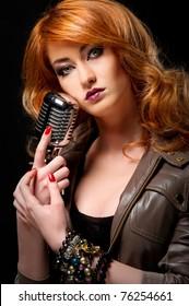 Beautiful redhead girl with retro microphone