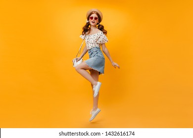 Beautiful redhead girl in summer denim outfit and straw hat holding white bag and jumping on orange background