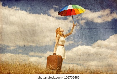Beautiful redhead girl with umbrella and suitcase at outdoor. Photo in old vintage style.