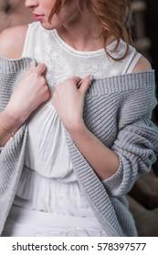 beautiful redhead girl in white dress grey cardigan close-up